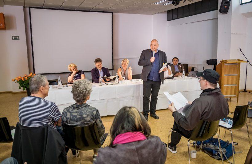 """Der Hausherr Boris Kochan begrüßt die Anwesenden und weist auf die Einmaligkeit des Ereignisses hin: """"Noch nie zuvor gab es in der Halle 27 Weißwürste und Blasmusik."""""""